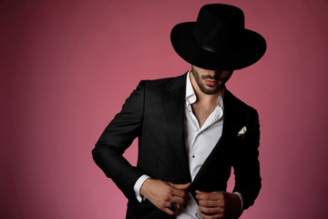 Elegant young man unbuttoning his shirt