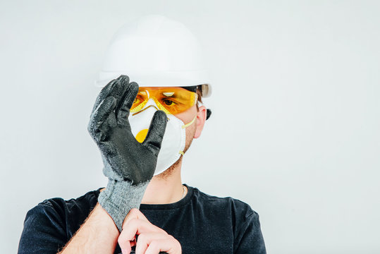 A worker wearing a protective helmet, protective goggles and a protective mask puts on protective gloves. Work concept, hiring workers for construction. Preparation to work.