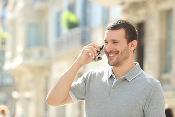 Happy adult man talking on phone in the street