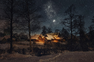 Beautiful night winter christmas landscape. View of snowy village houses lit by warm light from the window. Starry night and a hunch of Christmas.