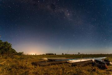 Botswanian local mokoro boats under the starlight sky, on the shore of delta Okavango river, Botswana