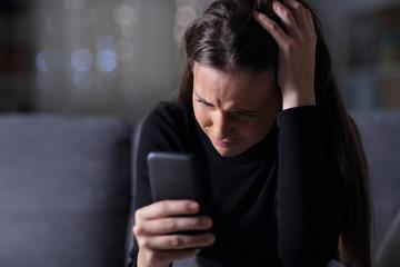 Sad girl checking bad news on mobile phone in the dark