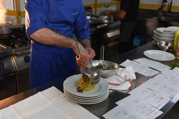 chef in cucina prepara una pentola di spaghetti ai frutti di mare