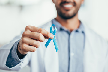 Prostate Cancer Awareness. Doctor man holding light Blue Ribbon for supporting people living and illness. Men Healthcare and World cancer day concept