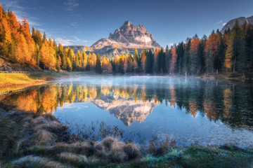 Aluminium Prints Mountains Lake with reflection of mountains at sunrise in autumn in Dolomites, Italy. Landscape with Antorno lake, blue fog over the water, trees with orange leaves and high rocks in fall. Colorful forest