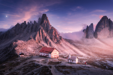 In de dag Alpen Mountains with beautiful house and church at sunset in autumn. Landscape with buildings, high rocks, purple sky with moon and clouds, sunlight. Mountains in fog. Tre Cime park in Dolomites, Italy