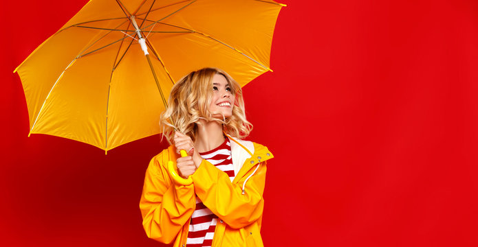 young happy emotional cheerful girl laughing and jumping with yellow umbrella   on colored red background.