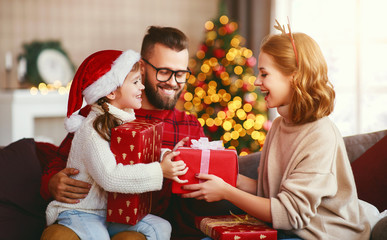 happy family with gifts near   Christmas tree at home.
