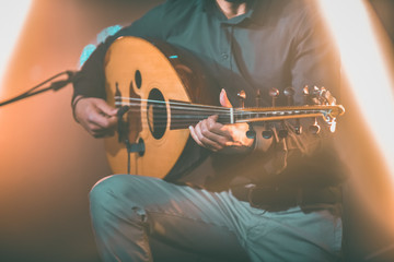 Toned image of musician playing traditional Turkish oud during concert with lights