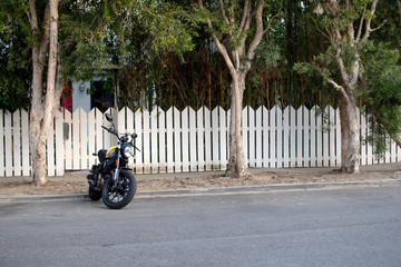 motorcycle parked in front of white fence and charming house
