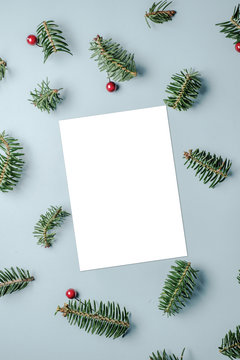 Blank card with fir tree branches red berries and star confetti on blue background