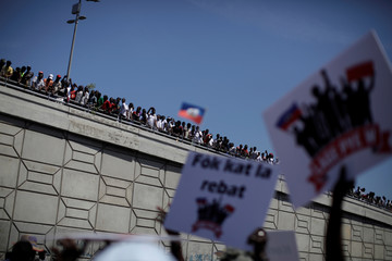 Protesters look from a bridge as other protesters march during a demonstration called by artists to demand the resignation of Haitian president Jovenel Moise, in the streets of Port-au-Prince