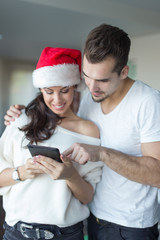 Happy young couple online shopping for Christmas on tablet at home
