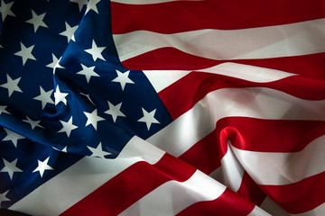 Close-up of ruffled American flag, light painted background - USA
