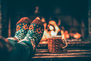 Acrylic Prints Relaxation Feet in woollen socks by the Christmas fireplace. Woman relaxes by warm fire with a cup of hot drink and warming up her feet in woollen socks. Close up on feet. Winter and Christmas holidays concept.