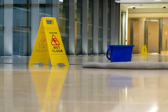 Yellow caution sign showing warning of slippery wet floor