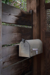 old mailbox on large plank wooden fence entryway