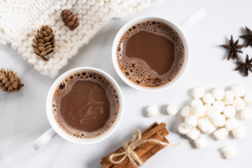 White ceramic cups of hot cocoa on top of white marble background, top view