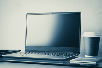 Laptop, notebook, pen and coffee cup on working desk or workspace. Free plain screen for copy space. Business, online education and e-learning, internet and technology, Tone and color adjustment.