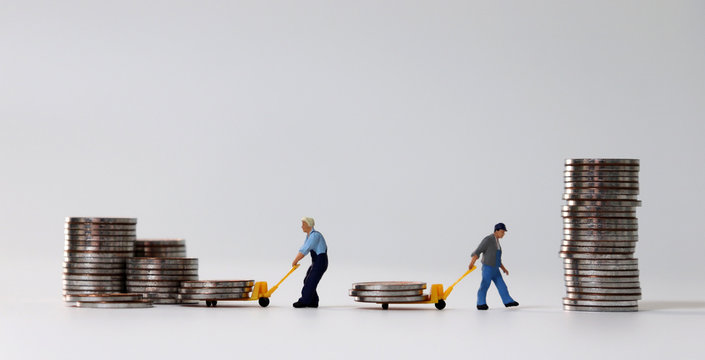 Miniature people pulling stack coins using for logistic.