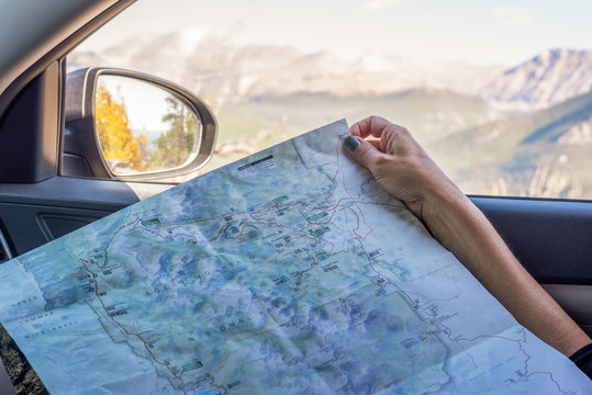 woman holding map while driving in Rocky mountain national park in Colorado