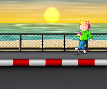 Boy walking listening music player on seaside