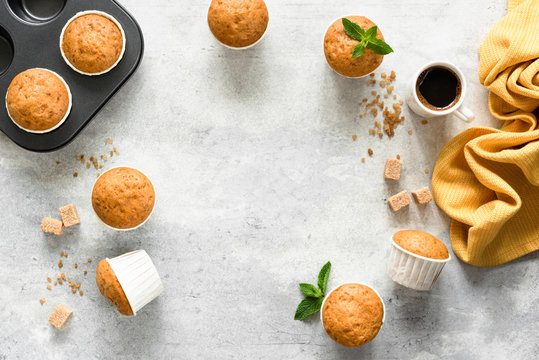 Homemade muffins in paper cups on concrete background. Vanilla muffins. Top view copy space
