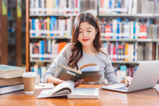 Asian young Student in casual suit doing homework and using technology laptop in library of university or colleage with various book and stationary over the book shelf background, Back to school