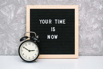 Your time is now. Motivational quote on letter board and black alarm clock on table against stone wall. Concept inspirational quote of the day