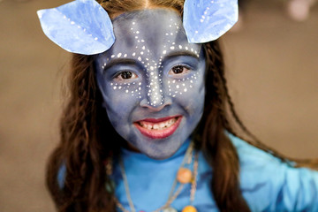 "A girl, with her face painted like a character from the movie ""Avatar"", poses for photographs during the Leisure and Fantasy Lounge ""SOFA"" in Bogota"