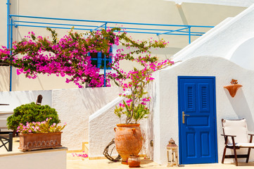 Traditional greek architecture and decor with pink flowers on Santorini island, Greece.