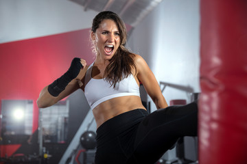 Female athlete fighter training, striking a bag in gym, intense self defense mixed martial arts training