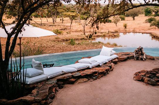 Swimming pool and African Safari lodge terrace in Savanna forest Serengeti Grumeti Reserve. Tanzania