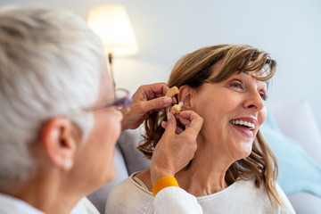 Otolaryngologist putting hearing aid in woman's ear on light background. Doctor Fitting Female Patient With Hearing Aid. Doctor inserting hearing aid in senior patient ear.