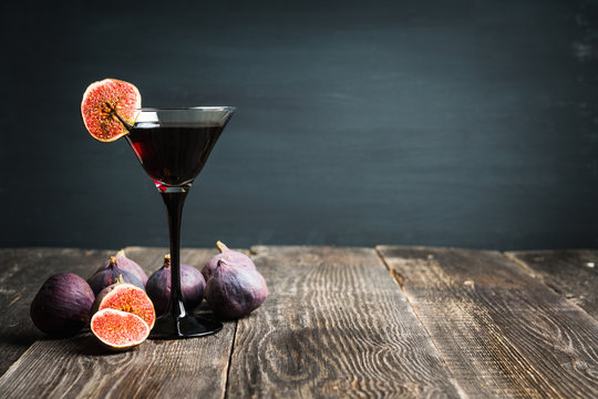 Martini cocktail with black vodka and figs on the rustic background. Selective focus. Shallow depth of field.