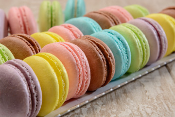 French colorful macarons on the wooden table.