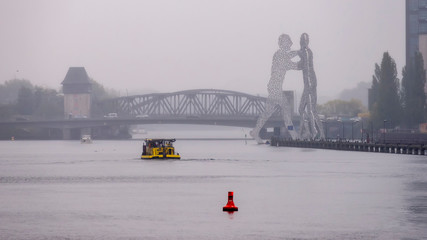 Spree river cruise on a typical winter day with rain and fog, near Molecule Man, Berlin, Germany