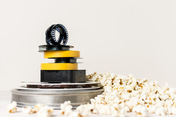 Stacked of film reels with film strip on top near the popcorn against white background