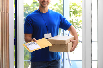 Young courier holding parcels on doorstep, closeup. Delivery service