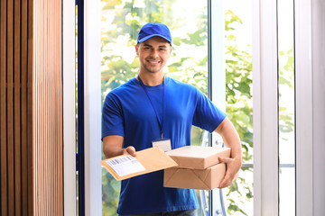 Young courier holding parcels on doorstep. Delivery service
