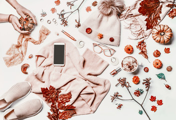 Autumn fashion woman clothes and shoes flat lay layout with smartphone mock up screen, sweater, knitted hat, scarf, eyeglasses, cosmetics,pumpkin,  cappuccino and fall leaves. Female hands.White desk