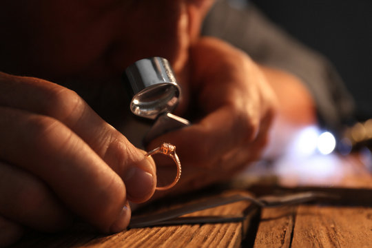 Male jeweler evaluating diamond ring in workshop, closeup view