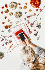 Woman holding smartphone with mock up screen on white desktop with notebooks, clipboard, fall leaves, pumpkins and cosmetics. Creative job layout. Home office. Top view.  Blogging. Autumn flat lay