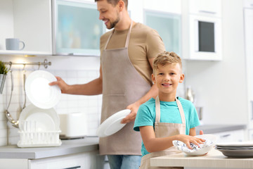 Dad and son wiping dishes in kitchen