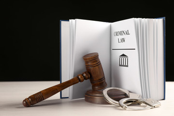 Judge's gavel, handcuffs and Criminal law book on white table against black background