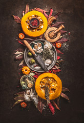 Autumn food arrangement composition with halved pumpkin , herbs , spices, knife and fall leaves on rustic background , top view.