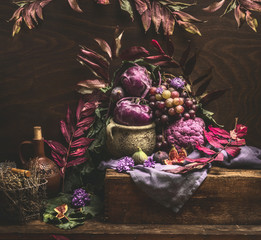 Still life with purple fruits and vegetables on wooden table with autumn leaves. Copy space for your design
