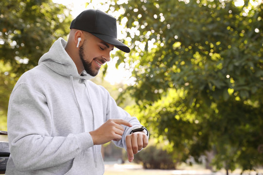Young man with wireless headphones and smartwatch listening to music in park. Space for text