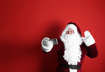 Authentic Santa Claus taking selfie on red background. Space for text