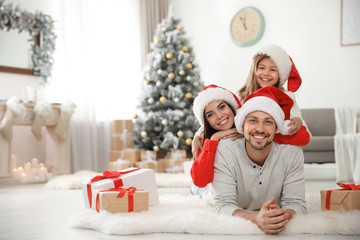 Portrait of happy family with Christmas gifts on floor at home